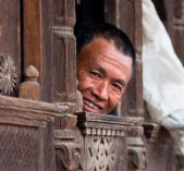 A man peeping form carved window